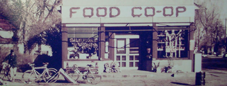 A faded photo shows bicycles and window displays at the original storefront of the Fort Collins Food Cooperative on Loomis and Mountain streets
