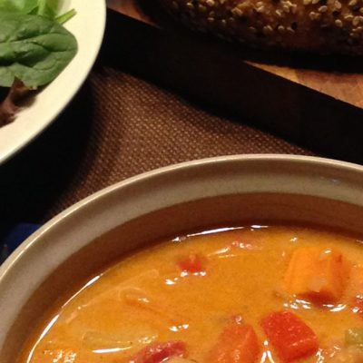 moroccan coconut chickpea soup recipe prepared and served with salad and a bread loaf